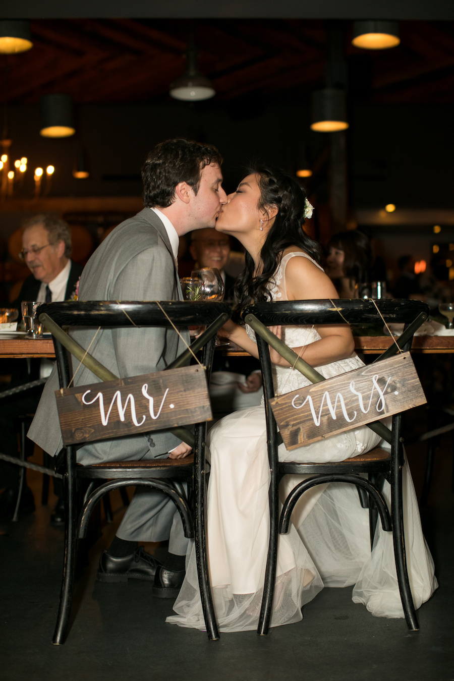 Bride and groom kissing sweetheart table Madera Kitchen