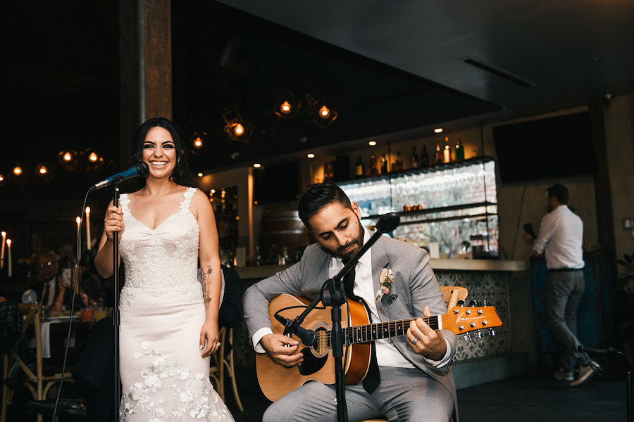 couple performing on stage at wedding in madera kitchen