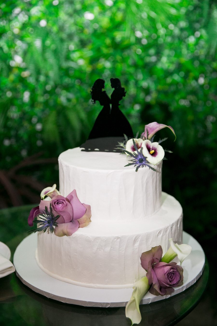 wedding cake with white and purple flowers