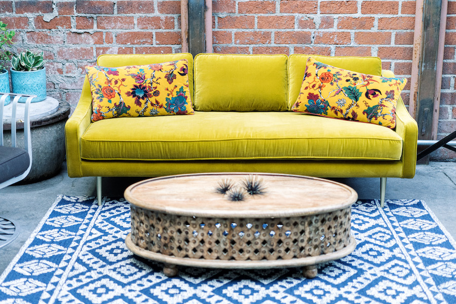 mustard colored couch with floral throw pillows