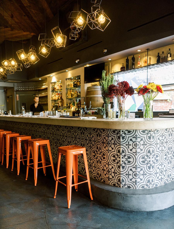 bar area at madera kitchen la with bright orange bar stools