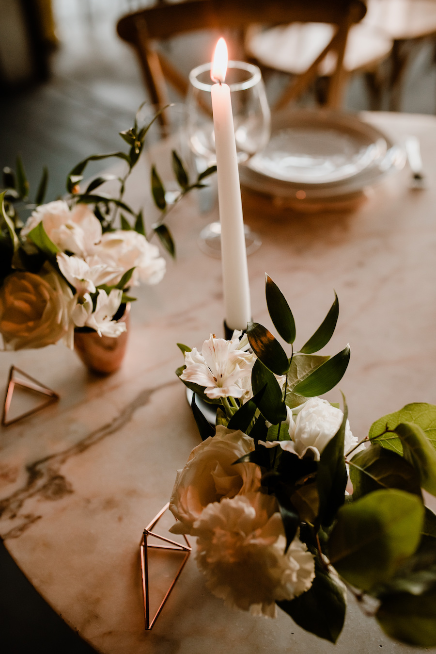 candle and floral bouquets on table at wedding reception