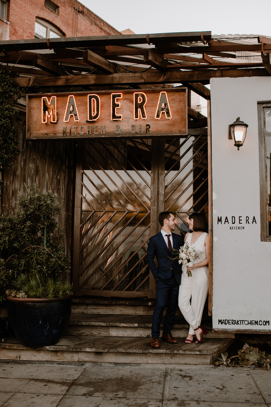 newlyweds standing outside of rustic restaurant in los angeles