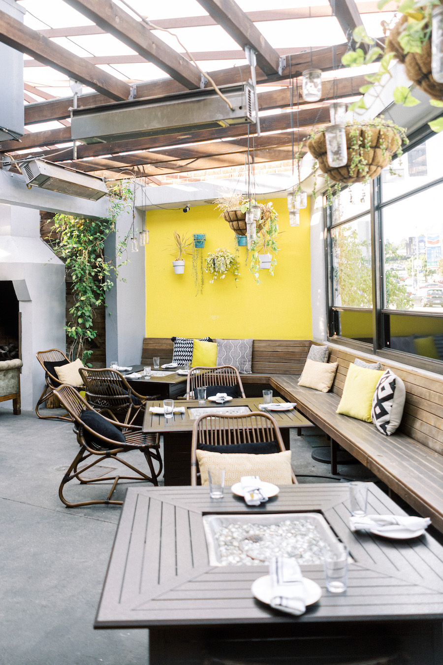 outdoor greehouse patio area in restaurant with yellow wall