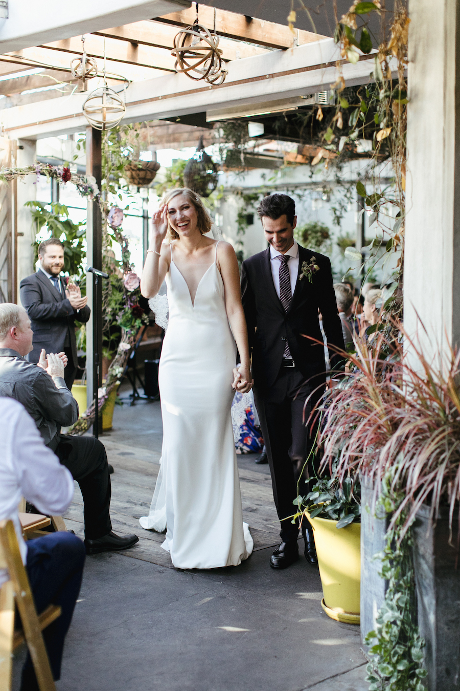 happy newlyweds walking down wedding aisle at madera kitchen la