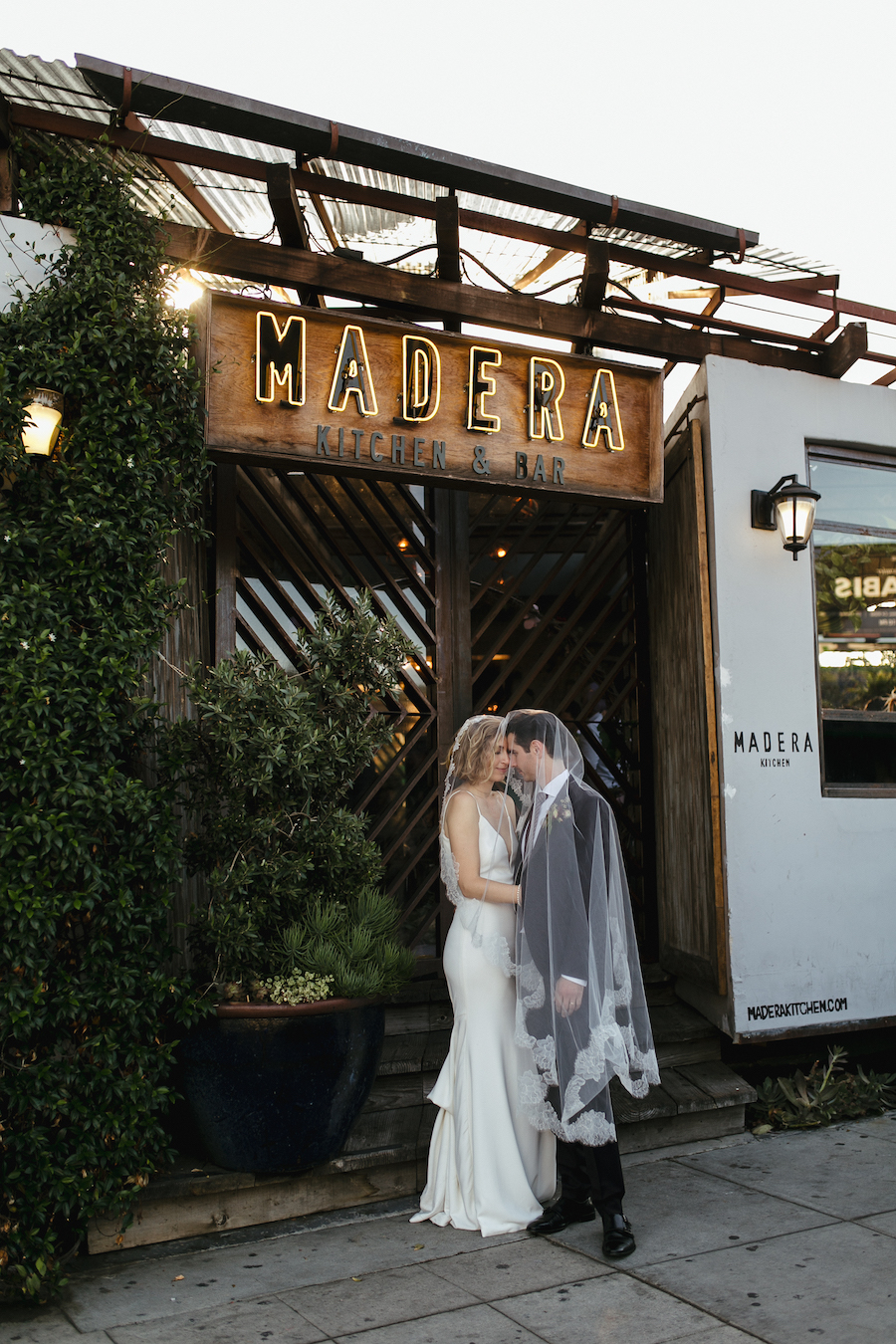 newlywed couple in front of madera kitchen los angeles