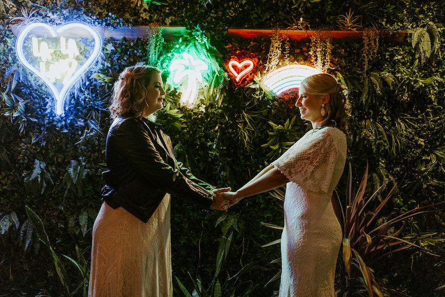 newlyweds posing in front of neon signs at wedding reception