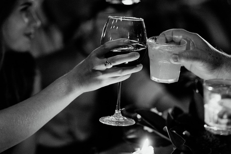 two people clinking drinks at wedding reception