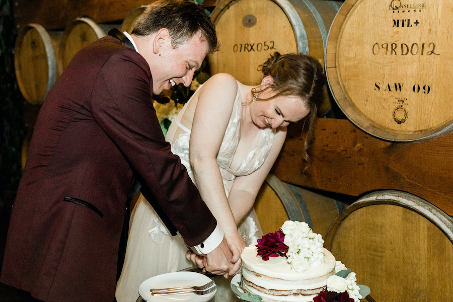couple cutting wedding cake together in los angeles