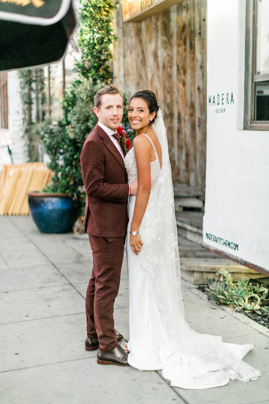 newlywed couple outside of restaurant in los angeles