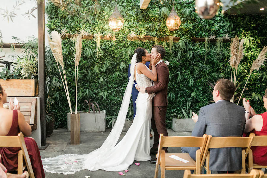 newlywed couple kissing at boho wedding venue