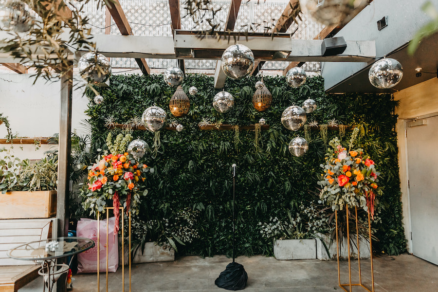 wedding ceremony decor with vibrant florals and disco balls